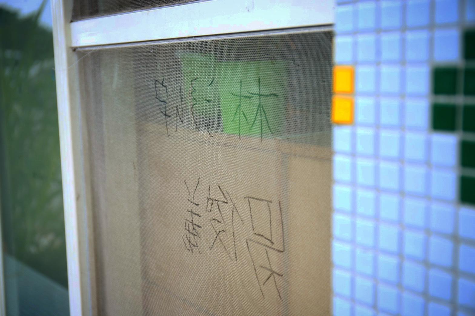 師傅帶著孩子一同裝修樹屋,孩子在自己修復完的紗窗寫下名字,以示負責。陳心慈攝影