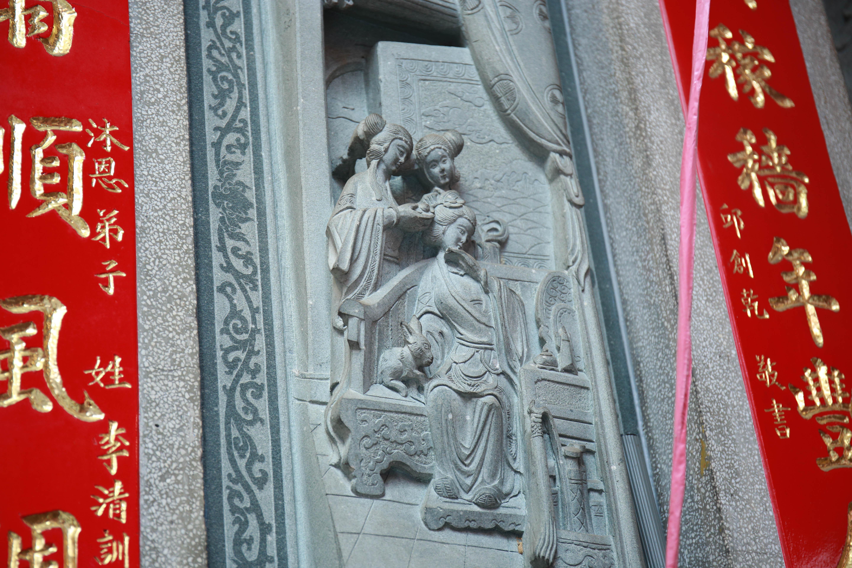 (廟宇的石雕分別大表不同的寓言故事,圖中寓言是訴說嫦娥追求美貌而失去珍貴東西。陳心慈攝影)