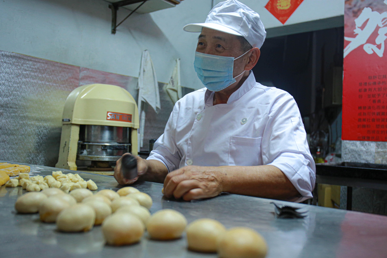 (新復昌食品行的師傅陳榮集正製作「月光餅」,擀麵的過程也與學於詳細介紹月光餅的來由。陳心慈攝影)