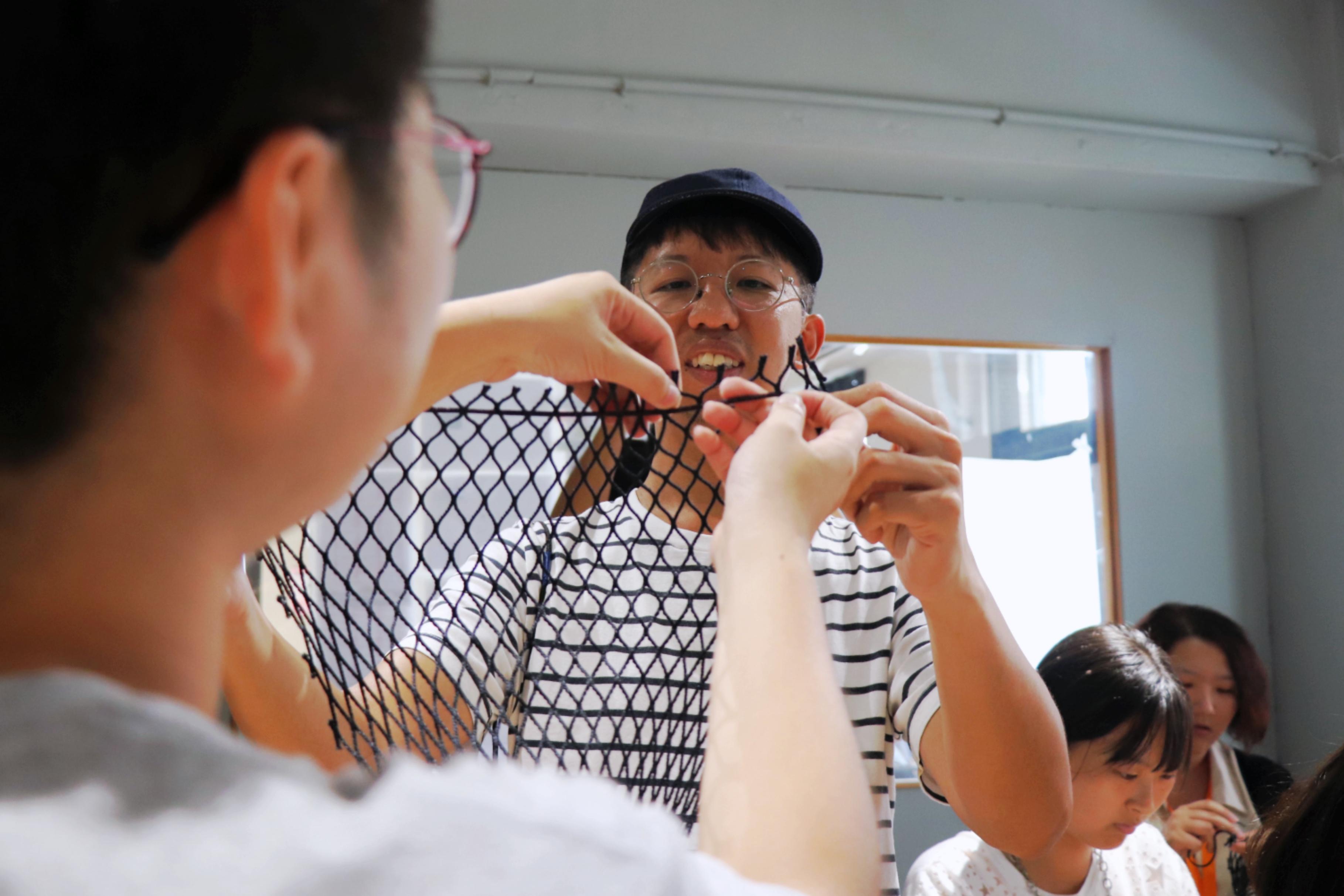 圖四:星濱山發起人林書豪示範如何製作漁網飲料袋,讓Dreamer學員實際體驗藝術共創的內涵。(攝/萬巧蓉)