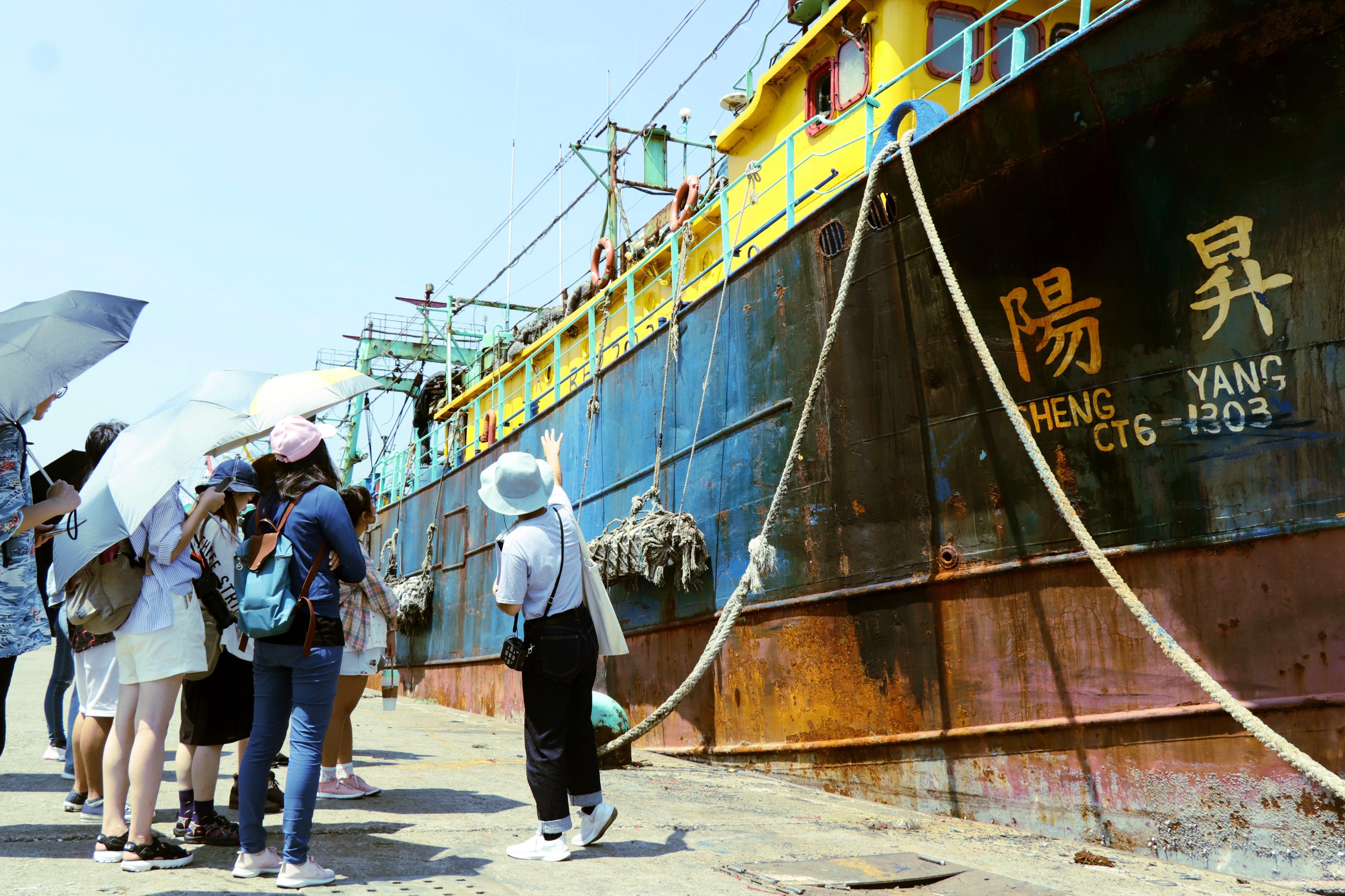 圖二:星濱山導覽員陳虹儒對Dreamer學員講解漁船的小知識,如:每艘漁船上有不同的數字標示,其實是船隻的身分證號。(攝/萬巧蓉)
